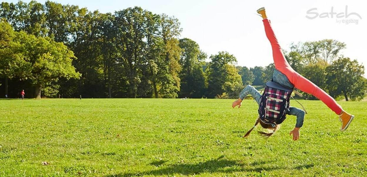 Satch - by ergobag - Mädchen mit Rucksack macht Radschlag